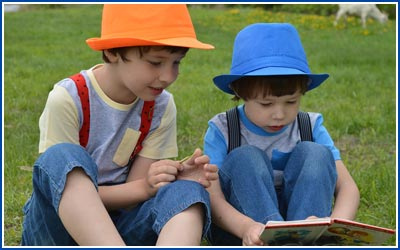 Two Boys reading a book while sitting on grass